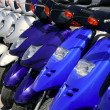 Scooter motorbikes in a row with perspective - Stock Photo