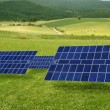 Clean electric energy solar plates in meadow - Stock Photo