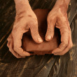 Artist man hands working red clay for handcraft - Stock Photo