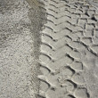 Stock Photo: Excavator tyres footprint on quarry white sand