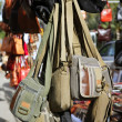 Bags hanging in market shop green khaki brown - Stock Photo