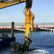 Marine dredging digging sea bottom black mud - Stock Photo