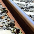 Iron rusty train railway detail over dark stones — Stock Photo #5505346