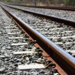 Iron rusty train railway detail over dark stones — Stock Photo #5505347