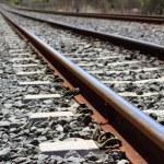 Iron rusty train railway detail over dark stones — Stock Photo