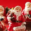 Three Santa Claus figurines over red background, studio - Stock Photo