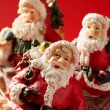 Three Santa Claus figurines over red background, studio — Stock Photo #5505536