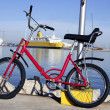 Bicycle parked in a harbour over blue water — Stock Photo