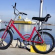Bicycle parked in a harbour over blue water — Stock Photo #5505600