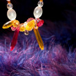 Stock Photo: Orange jewel necklace over blue purple feather