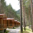 Forest wooden cabins in a mountain camping - Stock Photo