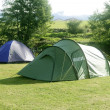 Camping tent field over green grass - Stock Photo