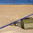 Royalty-Free Stock Photo: Fishing surfcasting rod and box over beach sand