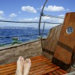 Royalty-Free Stock Photo: Man feet relax on golden wooden old sailboat