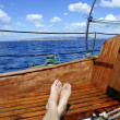 Man feet relax on golden wooden old sailboat — Foto de Stock