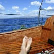 Man feet relax on golden wooden old sailboat — Stockfoto