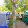 Camping tents caravan in green trees outdoor - Stock Photo