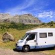 Camper van in mountains blue sky - Stok fotoğraf