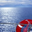 Stock Photo: Boat rail with round orange lifesaver blue sea