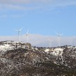 Aerogenerator windmills on snow mountain — Stock Photo