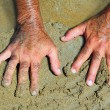 Hairy man hands on beach sand in sunny summer - Stock Photo