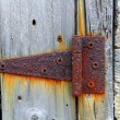 Royalty-Free Stock Photo: Rusty aged iron hinge weathered gray wood door