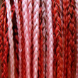 Artificial colorful braided hair red and pink — Stock Photo