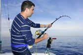 Angler fisherman fighting big fish rod and reel — Stock Photo
