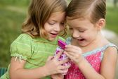Two little twin sisters playing with pink box — Stock Photo