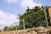 Fence on orange tree made of recycled bed structures — Stock Photo