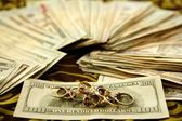 Dollar notes and gold rings over tablecloth — Stock Photo