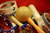 Mixed percussion toy instruments on red — Stock Photo