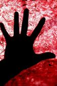 Backlight of human hand over red textured surface — Stock Photo
