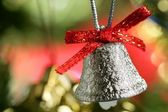 Silver bell in the christmas tree with red ribbon — Stock fotografie