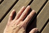 Man hand over sunny teak wood lines — Stock Photo