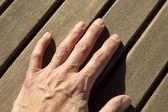 Man hand over sunny teak wood lines — Stock Photo