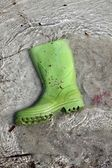 Green boots trash on beach shore pollution — Stock Photo