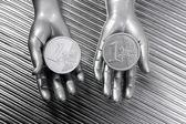 Deux pièces en euros dans les mains du robot futuriste d'argent — Photo