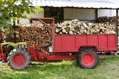 Firewood tractor in red color with stacked wood — Stock Photo