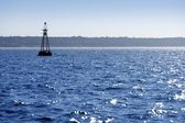 Beacon floating on blue ocean as guide help — Stock Photo