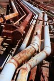 Aged rusty grunge industrial pipe lines — Stock Photo