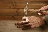 Carpenter hands with hammer wood and nail — Stock Photo