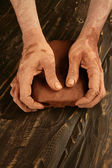 Artist man hands working red clay for handcraft — Foto Stock