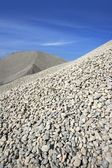 Gravel gray mound quarry stock blue sky — Stock Photo