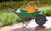 Gardener green wheel barrow with orange pail — Stock Photo