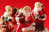 Three Santa Claus figurines over red background, studio — Stock Photo