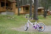 Chidren pink bicycle in wooden cabin mountain — Stock Photo