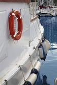 White boat side with fender and round lifesaver — Stock Photo