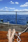 Man feet relax on golden wooden old sailboat — Stock Photo