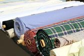 Colorful fabric rolls row in market shop — Stock Photo